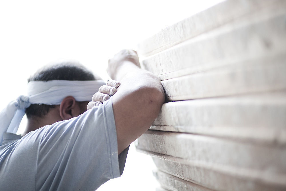 "Saed rests his head against a huge stack of pallets waiting to be filled with dough. The bakers work non stop with few breaks. One baker said, ""The worst part about the way we live is you loose time, I have lost my whole childhood working."""