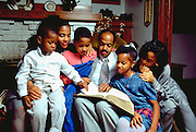 African American parents age 38 and 40 reading bible to kids, ages 5 through 15.  St Paul Minnesota USA