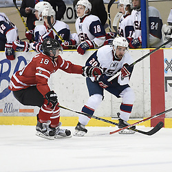 WELLINGTON, - Dec 11, 2015 -  Exhibition Game 2- Team Canada East vs Team USA at the 2015 World Junior A Challenge at the Wellington District Community Centre, ON. Tyler Rollo #18 of Team Canada East battles for control with Jake Wahlin #20 of Team United States during the first period.<br /> (Photo: Andy Corneau / OJHL Images)