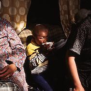 Mongolia. young boy drinking koumiss, cattle breeders  family inside the yurt (ger)  Ik Uul Sum      / Enfant d'éleveurs dans la yourte. durant un Petit Naadam à Ikh Uul Sum, dans l'aymag de Zavqan. Mongolie. L'arrivée d'un enfant dans une famille d'éleveurs est vécue comme un don du ciel. Quelques années plus tard il pourra aider activement ses parents dans de petites tâches quotidiennes, comme aller chercher de l'eau au puits, ou bien ramasser les argol, ou bouse séchée, qui sert de combustible à la maisonnée.  / R50/155    L0006217  /  P0007424