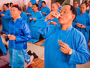 "09 FEBRUARY 2014 - HAT YAI, SONGKHLA, THAILAND: Men eat goat liver and drink Chinese rice wine in the Chao Mae Tubtim Shrine (Ruby Goddess Shrine) on 108 Hainanese Ancestors Memorial Day in Hat Yai, Songkhla, Thailand. Hainanese communities around the world celebrate ""108 Hainanese Ancestors Memorial Day."" The day honors the time when 109 Hainanese villagers fleeing life in Hainan (an island off of the southwest coast of China, near Vietnam) washed up in what is now Vietnam and were killed by Vietnamese authorities because authorities thought they were pirates. The Vietnamese built a temple on the site and named it ""Zhao Yin Ying Lie."" Many Vietnamese fisherman credit prayers at the temple to saving their lives during violent storms and now ""108 Hainanese Ancestors Memorial Day"" is celebrated in Hainanese communities around the world. Hat Yai, the economic center of southern Thailand has a large Hainanese population.    PHOTO BY JACK KURTZ"