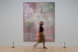 "© Licensed to London News Pictures. 30/05/2019. LONDON, UK. A staff member poses next to ""Raining Down South"", 1968, by Frank Bowling at a preview of works by artist Frank Bowling (born in Guyana in 1934).  The retrospective exhibition spans his six-decade career and takes place 31 May to 26 August 2019 at Tate Britain.  Photo credit: Stephen Chung/LNP"