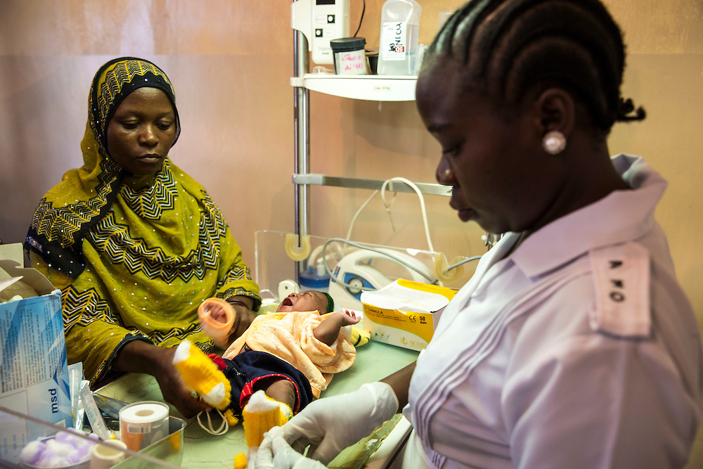 A nurse attends to 3 day old baby Brighton who has a fever, carefully watched by Francisca Peter the mother on the infrared baby warming machine on the NICU (Neonatal Intensive Care Unit) Ward. St Walburg's Hospital, Nyangao. Lindi Region, Tanzania.