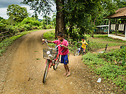 21 JUNE 2016 - DON KHONE, CHAMPASAK, LAOS: Boys ride their bikes on Don Khone Island. Don Khone Island, one of the larger islands in the 4,000 Islands chain on the Mekong River in southern Laos. The island has become a backpacker hot spot, there are lots of guest houses and small restaurants on the north end of the island.       PHOTO BY JACK KURTZ