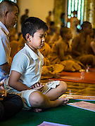 03 APRIL 2016 - CHIANG MAI, THAILAND: A Thai boy participates in a meditation and prayer at Wat Chedi Luang in Chiang Mai. The meditation ceremony was in honor of the birthday of Her Royal Highness Princess Maha Chakri Sirindhorn, the daughter of Bhumibol Adulyadej, the King of Thailand. The Princess was born on April 2, 1955. She is revered by Thais and special ceremonies in her honor are held in temples throughout Thailand.      PHOTO BY JACK KURTZ