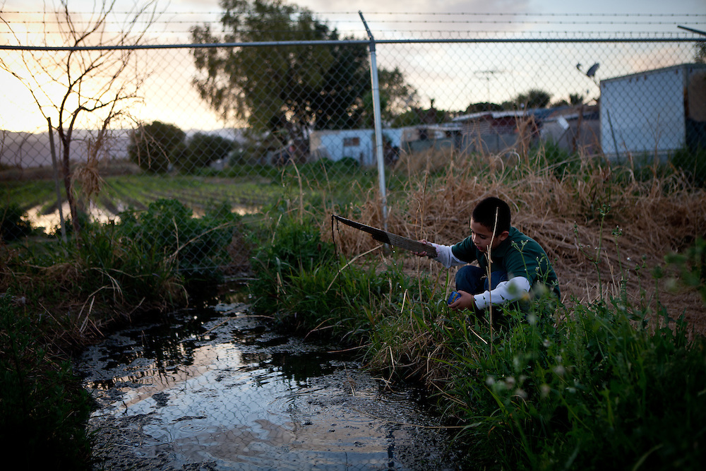 Seven-year-old Naftale Gutierrez plays in raw sewage that flows from the Rancho Garcia trailer park onto adjoining agricultural land in Thermal, Calif., March 8, 2012. Across California there are hundreds of unincorporated communities like Thermal. While a few are some of the state's richest areas; most lack sewer systems, clean drinking water, sidewalks, street lights, and storm drains. Populated by poor, working class Latinos, they're neglected by local government and lack the resources to install the most basic infrastructure that city residents rely on.<br />