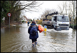Residents walk in the flood hit streets as floods hit Egham, United Kingdom, Wednesday, 12th February 2014. Picture by Andrew Parsons / i-Images