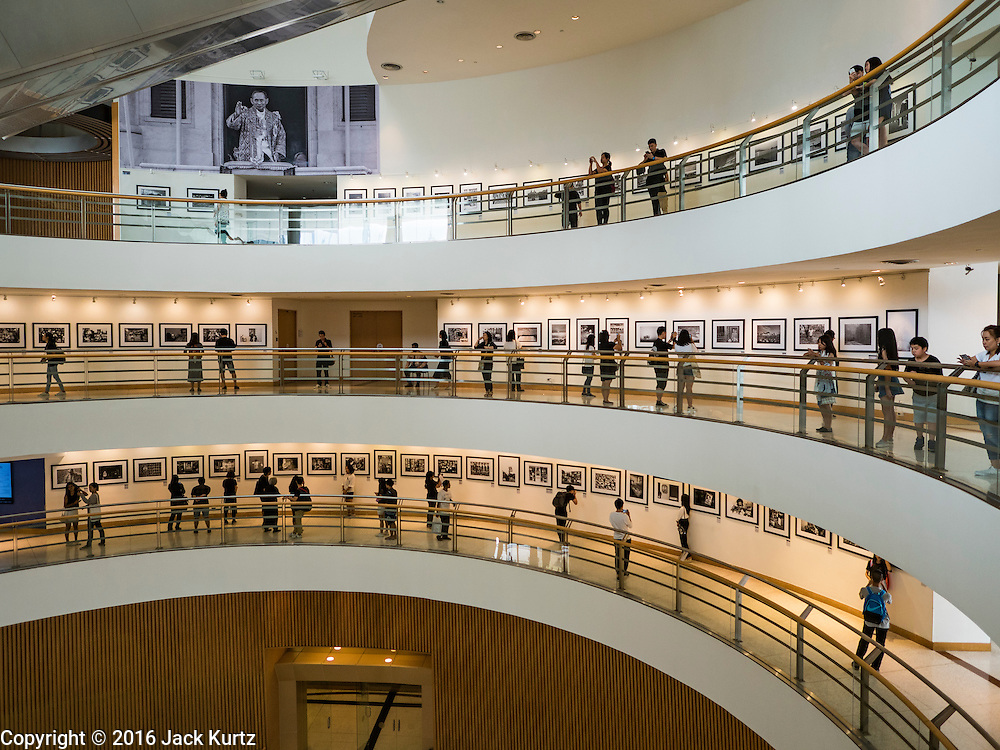 "06 NOVEMBER 2016 - BANGKOK, THAILAND: People walk through a photo exhibit honoring Bhumibol Adulyadej, the late King of Thailand at the Bangkok Art and Culture Centre. The Royal Photographic Society of Thailand with the Bangkok Art and Culture Centre and Thai Beverage Public Company Limited are hosting a photography exhibition to commemorate the late Thai King Bhumibol Adulyadej. The ""In Remembrance of His Majesty King Bhumibol Adulyadej"" Photography Exhibition is dsiplaying 89 photographs by 89 photographers honoring King Bhumibol Adulyadej's legacy. The King was an avid photographer was usually seen with a camera in his hands. The exhibition will be on display until 27 November 2016 on the Curved Walls on the 3rd - 5th floor, Bangkok Art and Culture Centre.     PHOTO BY JACK KURTZ"
