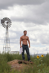 shirtless muscular man standing near a windmill on a ranch in New Mexico