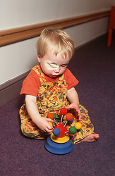 Young child with visual impairment playing with toy,