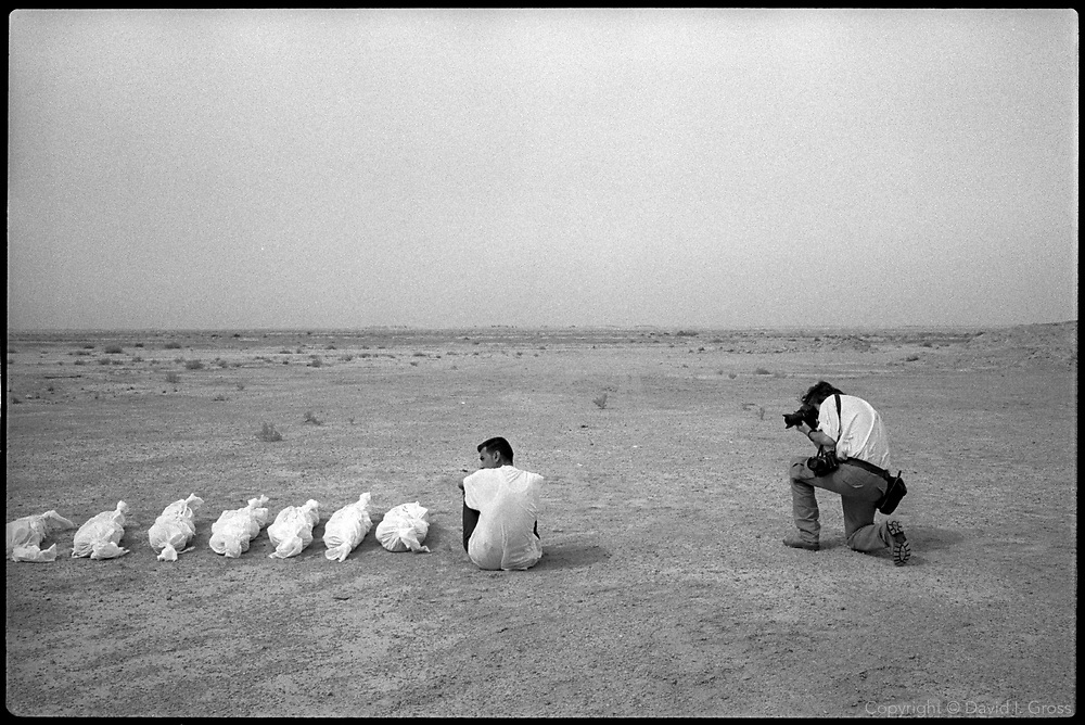 A photojournalist, Bruno Stevens, shoots the shrouded bones and a worker at a mass grave near Al-Musayab, Iraq. Journalists were called upon to show how the exhumations were being handled.