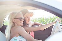 Happy female friends enjoying in car on sunny day