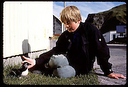 Boy sits in grass beside flightless puffin chick he rescued for release at sea; August/Westmann Iceland