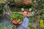 Kevin Forltey of Giant Veg with a large beetroot on The Facebook Beyond the Screen garden - Press preview day at The RHS Chelsea Flower Show.