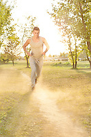 Full length of man listening music while running in park