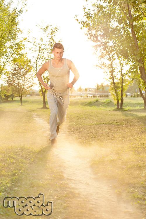 Full length of man listening music while running in park