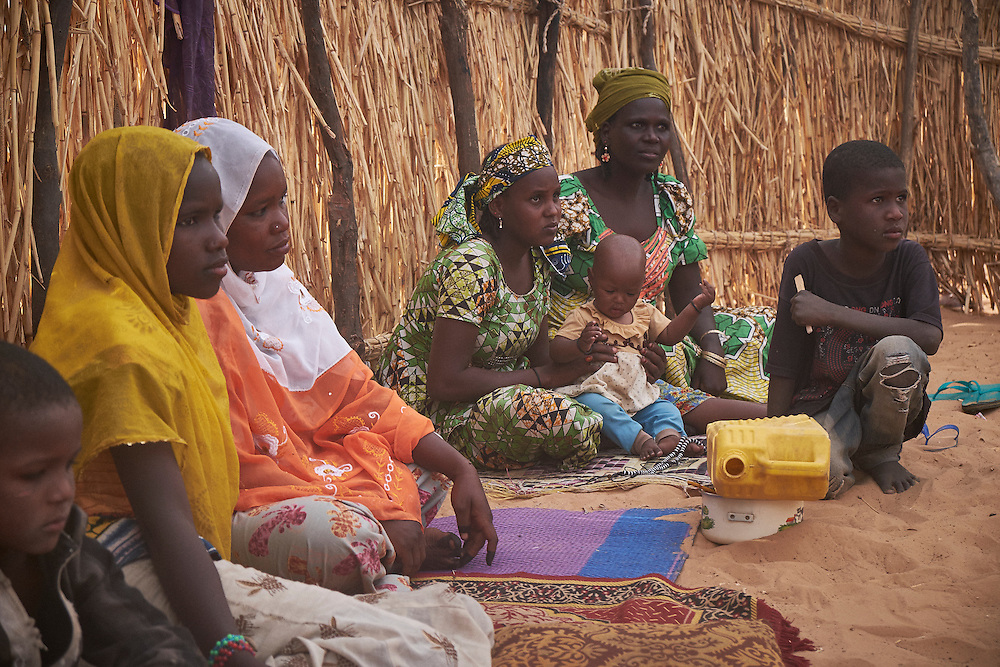 3 wives with their children at a camp of displaced people in the neighbourhood of Chateau, Diffa, Niger on February 13, 2016. The camp is mixed between displaced people from Niger, Nigeria and Chad. They have fled attacks by the militant group Boko Haram on their villages and it's ongoing conflicts with the armies of each country. Caritas undertook a distribution of mosquito nets, cooking pots, sleeping covers, hygiene kits, clothes and cash transfers to the displaced. 228 households received support from Caritas among an estimated 1500 households in the  vicinity of Chateau. There is still great need. There is no school system in place for the children and the housing is not adequate for many as more people arrive each day escaping hostilities. <br /> <br /> 'We arrived here from Chad one month before because we were so scared of being attacked in the village. It took three days to walk here. We need more food, medicine and materials for building a shelter that will protect us when the rain comes. We feel secure here for the moment because of the army's presence but we have no intention of going home soon.'
