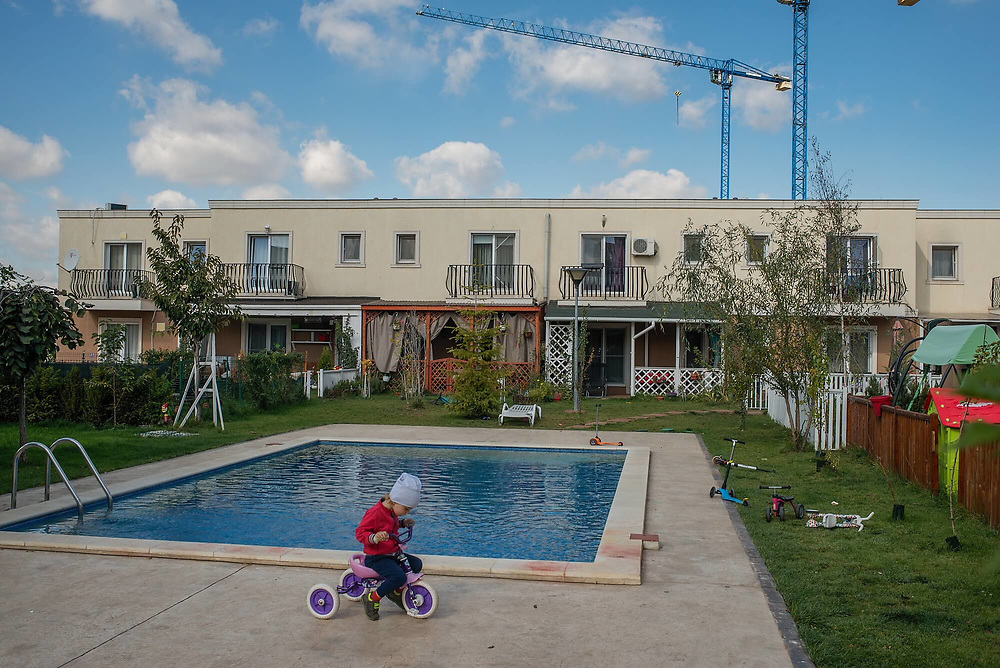 A child rides a scooter in the gated community of Cosmopolis.