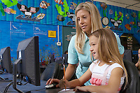 School girl using computer with teacher in classroom