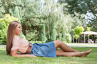 Full length of happy young woman reclining on grass in park