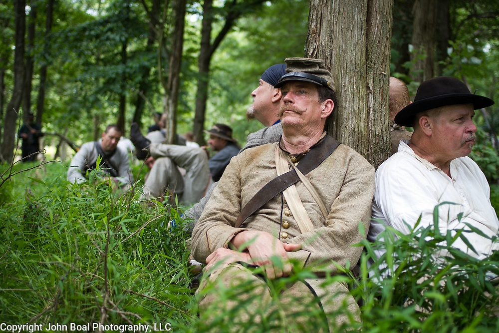 John King, of Gillsville, Georgia, rests his head against a tree, prior to participating in a reenactment of Pickett's Charge, as part of the 47th North Carolina, during the Sesquicentennial Anniversary of the Battle of Gettysburg, Pennsylvania on Sunday, June 30, 2013.  A pivotal moment in the Civil War, over 50,000 soldiers died in the battle which spanned 3 days from July 1-3, 1863.  Later that year, President Abraham Lincoln returned to Gettysburg to deliver his now famous Gettysburg Address to dedicate the cemetery there for the Union soldiers who died in battle.  John Boal photography