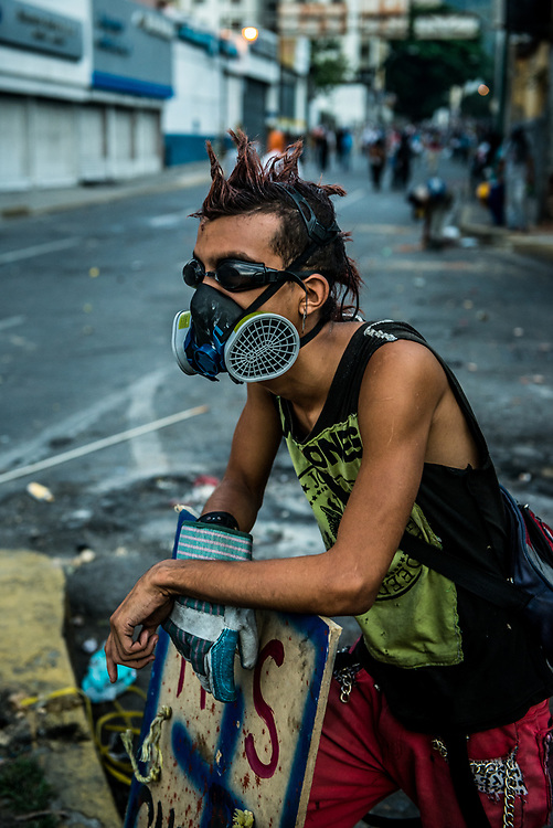 CARACAS, VENEZUELA - JUNE 2, 2017:  Anti-government protesters use homemade shields and throw rocks and molotov cocktails at security forces, who responded by heavily tear gassing and firing rubber bullets and buckshot at them.  The streets of Caracas and other cities across Venezuela have been filled with tens of thousands of demonstrators for nearly 100 days of massive protests, held since April 1st. Protesters are enraged at the government for becoming an increasingly repressive, authoritarian regime that has delayed elections, used armed government loyalist to threaten dissidents, called for the Constitution to be re-written to favor them, jailed and tortured protesters and members of the political opposition, and whose corruption and failed economic policy has caused the current economic crisis that has led to widespread food and medicine shortages across the country.  Independent local media report nearly 100 people have been killed during protests and protest-related riots and looting.  The government currently only officially reports 75 deaths.  Over 2,000 people have been injured, and over 3,000 protesters have been detained by authorities.  PHOTO: Meridith Kohut