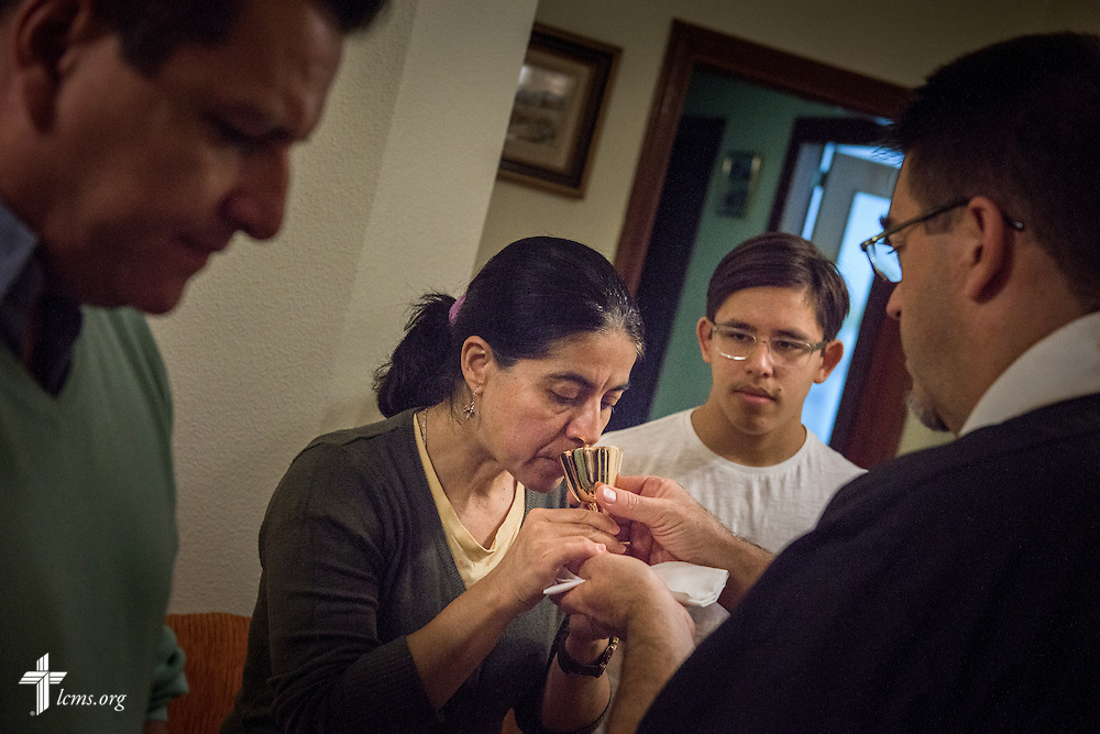 The Rev. David Warner, LCMS career missionary to Spain,  distributes the Sacrament to Sandra María and her family, Jose Antonio (left) and Juan José, during home worship at the family's home Friday, Nov. 4, 2016, in Valladolid, Spain. LCMS Communications/Erik M. Lunsford
