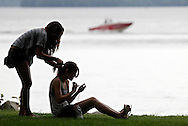 Cornwall-on-Hudson, New York - A girl sits on the grass and looks at photos on her digital camera while her friend braids her hair during the RiverFest at Donahue Park on the shore of the Hudson River on June 4, 2011.