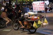Meals on Wheels: a food vendor carrying his stove and meal ingredients on the back of a motorcycle on Nguyen Hue Boulevard in Ho Chi MInh City, Vietnam