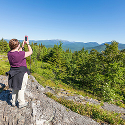 A woman captures a cell phone picture of Mount Washington in the distance in Jackson, New Hampshire. White Mountains.