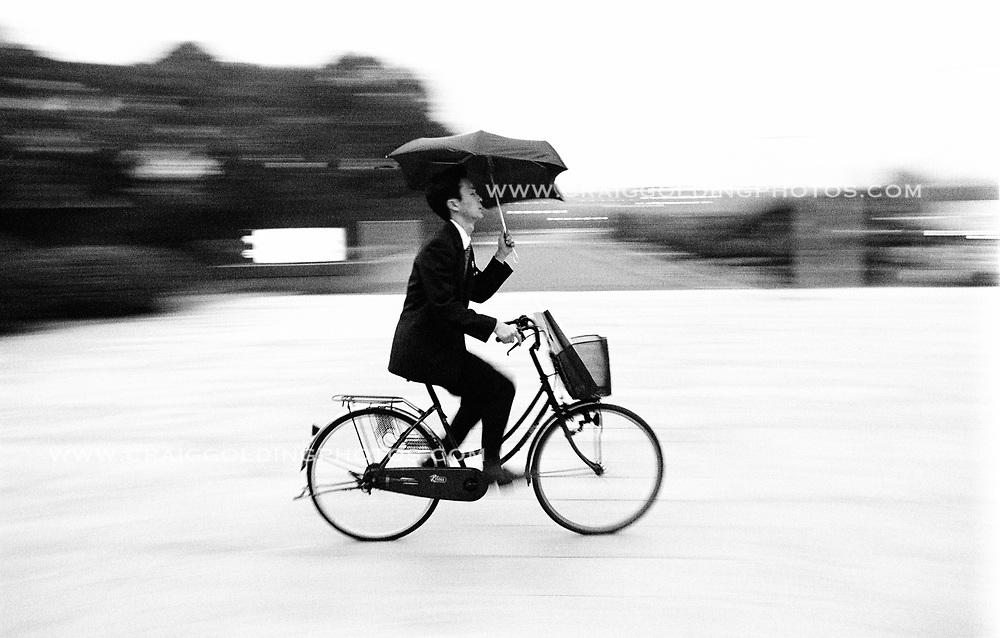 Buisnessman rides his bike in the rain in Tokyo, Japan.