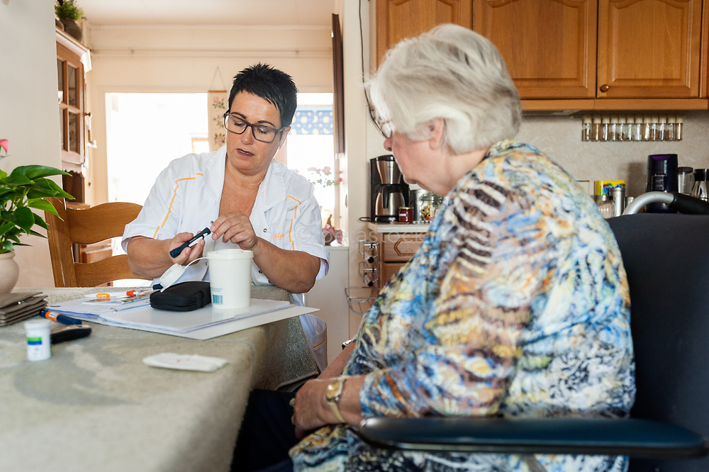 Homecare nurse performing a  finger prick test for blood glucose y an older patient. Thuiszorg verpleegkundige tijdens een diabetes test thuis bij de patient.