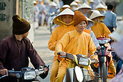08 MARCH 2006 - HO CHI MINH CITY, VIETNAM: Buddhist nuns on motorscooters leave a temple in Ho Chi Minh City, Vietnam. HCMC is still widely known as Saigon. Rapid economic development in southern Vietnam has allowed many people who used to rely on bicycles for transportation to upgrade to motorscooters and motorcycles.  PHOTO BY JACK KURTZ