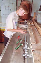 Teenage boy learning plumbing skills,