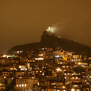 A view from Santa Teresa in the hills of Rio de Janeiro as The iconic Cristo Redentor, Christ the Redeemer statue appears out of the clouds while lit up at night time atop the mountain Corcovado. In the foreground is the Favela Morro da Coroa. Many favela's scatter the hillsides around Rio while The iconic statue of Christ can be seen for miles around the city. Rio de Janeiro, Brazil. 3rd October 2010. Photo Tim Clayton..