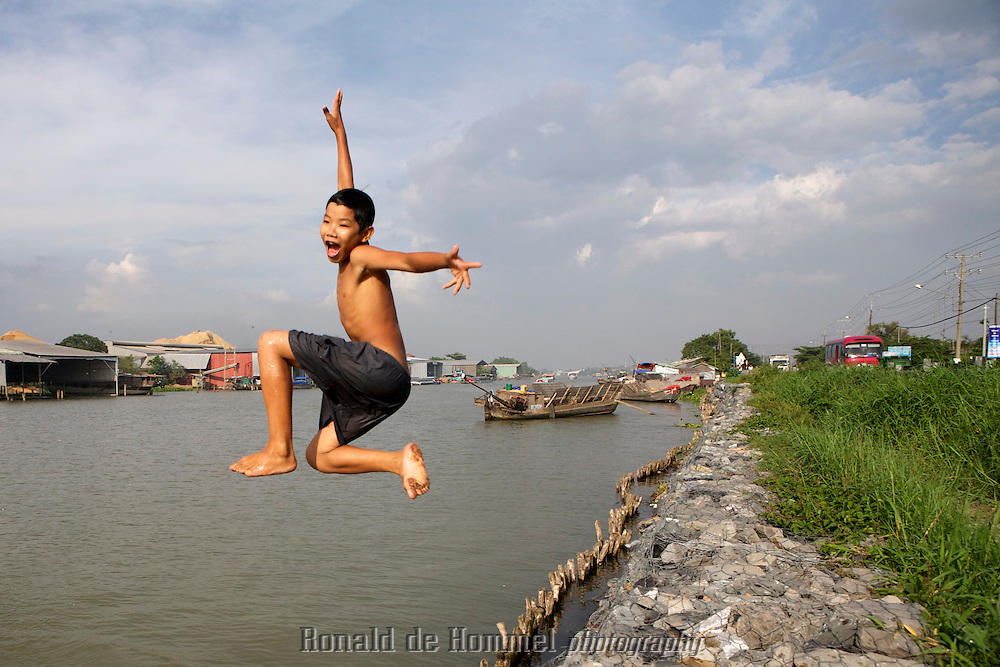 A boy jumps in the water of one of the arms of the Mekong River in the delta in southern Vietnam. The river is the main transportation highway in the south of the country. Pollution, the building of dams upstream and a changing climate have affected the amount of fish in the water dramatically.
