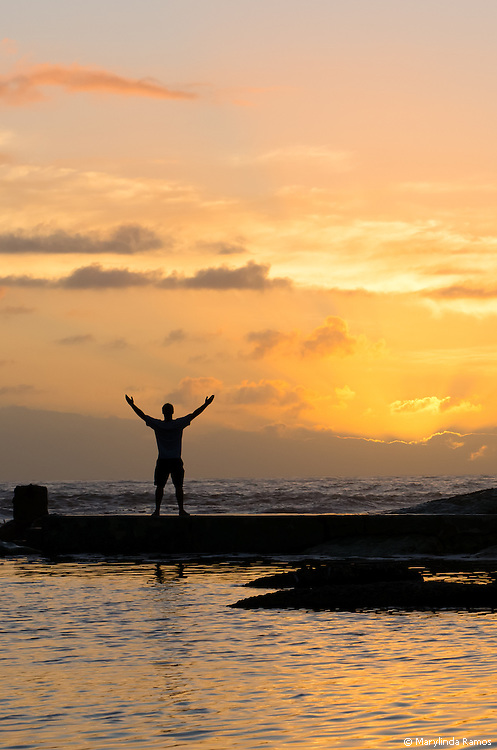 Sillouette of a man at the edge of a tidal pool facing the ocean and an orange sunset, with arms up and outstretched in a gesture that could be interpreted as gratitude, joy, admiration, welcome or hope.