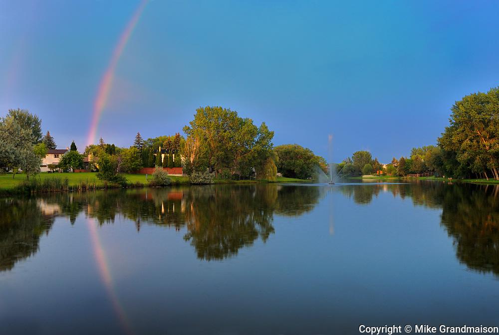 Rainbow reflected in pond in Southdale Neighbourhood<br />Winnipeg<br />Manitoba<br />Canada
