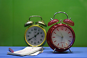 two old type wmechanicl alarm clock on green background