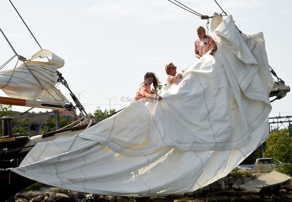 7/20/16 :: REGION :: STAND ALONE :: Deckhands on the schooner Mystic Whaler, from left, Ann Marie Carton, Lindsay Unruh and A.J. Jacobsen furl the jib following a day sailing in Long Island Sound Wednesday, July 20, 2016. The Whaler is a reproduction of a 19th century coastal cargo schooner built in Florida in 1967 and cruises from the New London waterfront six days a week. (Sean D. Elliot/The Day)