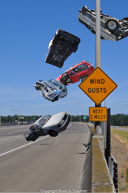 Humorous photograph of a WIND GUSTS warning sign with cars blowing off the road and up in the air behind the sign.