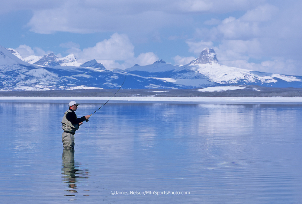 08443-L. An angler casts a fly for large trout during the early spring ice-out on Duck Lake on the Blackfeet Indian Reservation in northwest Montana.