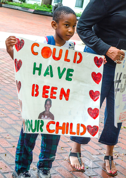 "Sevyn Coleman, 5, stands outside the Florida Capitol building in Tallahassee, July 20, 2013, holding a sign featuring an image of 17-year-old Trayvon Martin, who was fatally shot in early 2012. Coleman was with his mother, Dana Coleman, who was participating in a rally against racial profiling and Florida's ""stand-your-ground"" self-defense law.  (Photo by Carmen K. Sisson)"