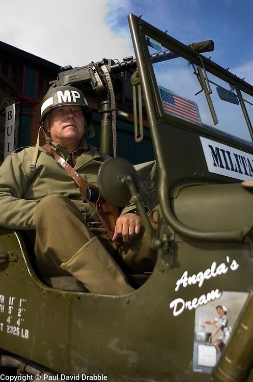 A reenactor portrays a sergeant from the American 101st Airborne &quot;Screaming Eagles&quot; armed with a Colt 45 Automatic Pistol carried in a shoulder holster and wearing an MP (Military Police) steel helmet  <br /> 4 September 2009  Copyright Paul David Drabble