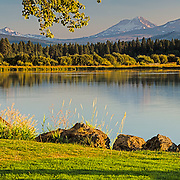 The Three Sisters - South, Middle, and North from the shore at Black Butte Lodge.  A panorama made at sundown and in a golden glow.