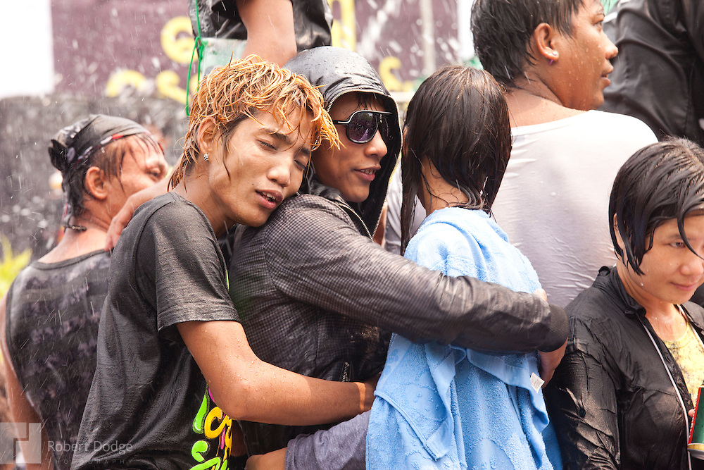 Mandalay, Myanmar- April 14, 2013: Young people, who climbed atop a moving vehicle to dance and get hosed by water during Myanmar's Thingyan Water Festival, also shared some affection with their friends as they celebrated the New Year. Thingyan is held in April, one of the hottest months of the year in Myanmar. The water festival marks the country's New Year celebration and the festival includes lots of drinking, singing, dancing and theater. Wherever you are you are likely to get doused with water as the Burmese see this as a cleansing of the previous year's sins and bad luck and a blessing for good luck and prosperity in the year ahead. In the major cities of Mandalay and Yangon, large platforms are erected along major roadways and are equipped with high powered water hoses. The platforms, sponsored by large corporate donors, also have dance stages and play the latest pop and hip hop music. Thousands of residents pour into the streets by foot, motorbike and flatbed truck to get hosed under the platforms while they drink and dance. Many of the young celebrants wear their best clubbing clothes. And many of the party goers are men, having left their wives and girlfriends at home.