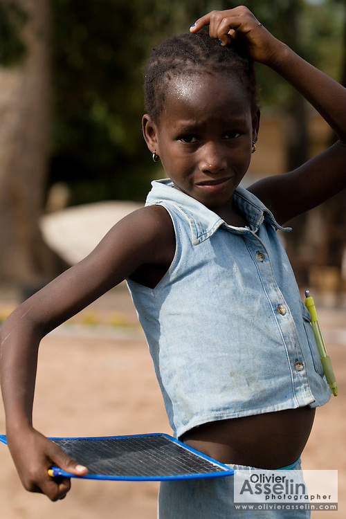 A girl holding her small chalk board as she stops on her way home from school near the village Mpack, on the border with Guinea-Bissau, southern Senegal, on Thursday June 14, 2007.