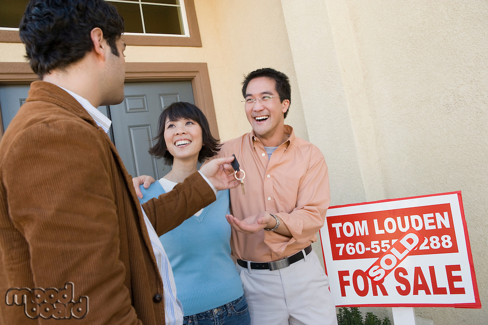 Mid adult couple receiving keys to their new home