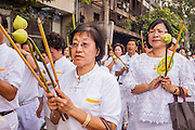 14 OCTOBER 2012 - BANGKOK, THAILAND:    Women in white, signifying that they have pledged to not eat meat for the Vegetarian Festival process through Bangkok on the first day of the Vegetarian Festival. The Vegetarian Festival is celebrated throughout Thailand. It is the Thai version of the The Nine Emperor Gods Festival, a nine-day Taoist celebration beginning on the eve of 9th lunar month of the Chinese calendar. During a period of nine days, those who are participating in the festival dress all in white and abstain from eating meat, poultry, seafood, and dairy products. Vendors and proprietors of restaurants indicate that vegetarian food is for sale by putting a yellow flag out with Thai characters for meatless written on it in red.    PHOTO BY JACK KURTZ