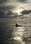 Vanessa Yeager paddles out as the sun sets over Newport Beach, Calif.